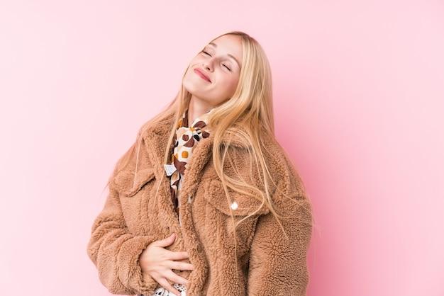 De jonge blondevrouw die een laag dragen tegen een roze muur raakt buik, glimlacht zacht, het eten en tevredenheidsconcept.