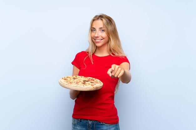 De jonge blondevrouw die een pizza over geïsoleerde blauwe muur houden richt vinger op u met een zekere uitdrukking