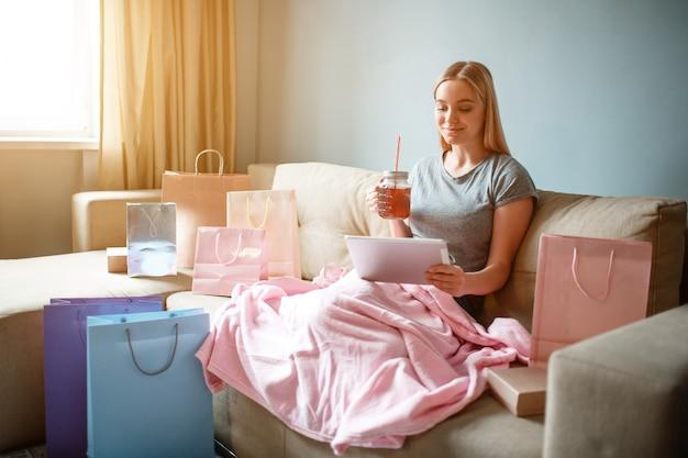 De jonge blondevrouw met thee bekijkt tablet en kiest goederen in online winkel terwijl het zitten met deken op een bank
