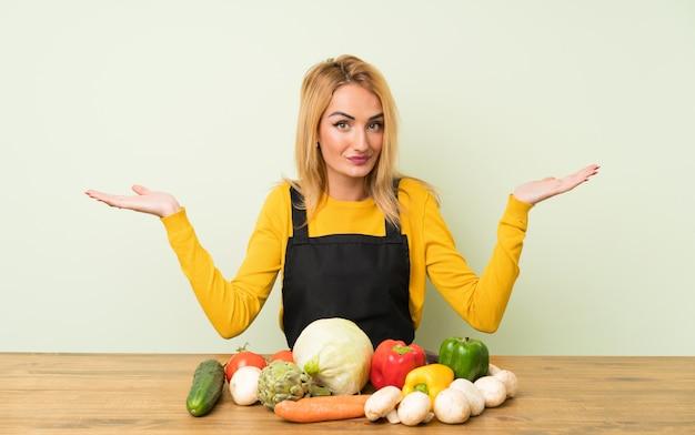 De jonge blondevrouw met veel groenten die twijfels hebben met verwart gezichtsuitdrukking