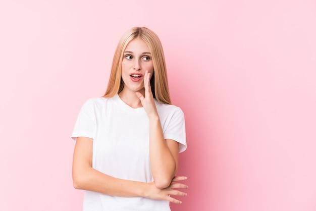 De jonge blondevrouw op roze achtergrond zegt een geheim heet remmend nieuws en kijkt opzij