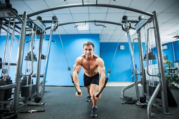 De jonge bodybuilder werkt aan zijn borst met kabeloversteekplaats in gymnastiek