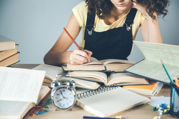 De jonge boeken van de meisjeshand op bureau
