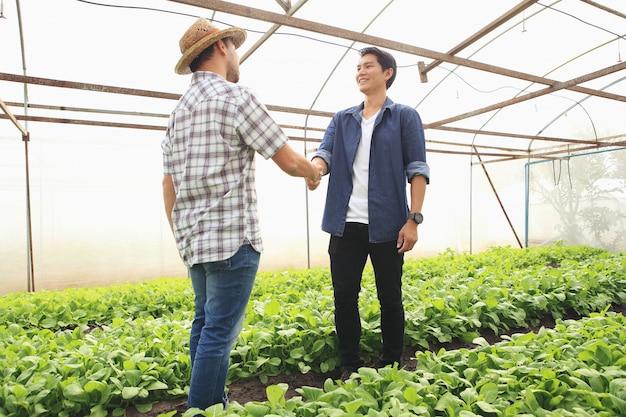 De jonge boeren schudden elkaar de hand om de klanten te feliciteren nadat de onderhandelingen succesvol zijn verlopen.