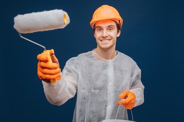 De jonge bouwer houdt rol vast om muur en glimlach te schilderen