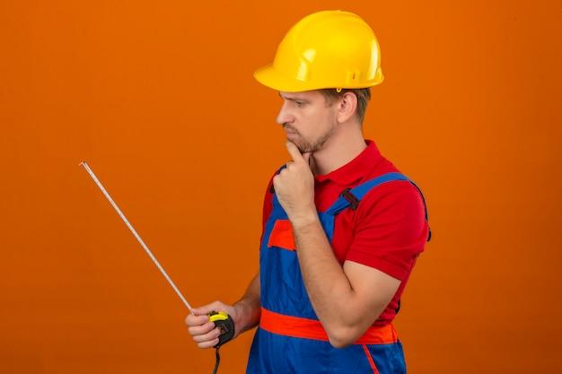 De jonge bouwersmens in eenvormige bouw en veiligheidshelm die bij het meten van band in zijn peinzende handen kijken kijken over geïsoleerde oranje muur