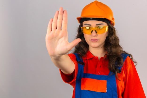 De jonge bouwersvrouw in bouw eenvormige gele glazen en veiligheidshelm die einde doen zingen met palm van de uitdrukking van de handwaarschuwing over geïsoleerde witte muur