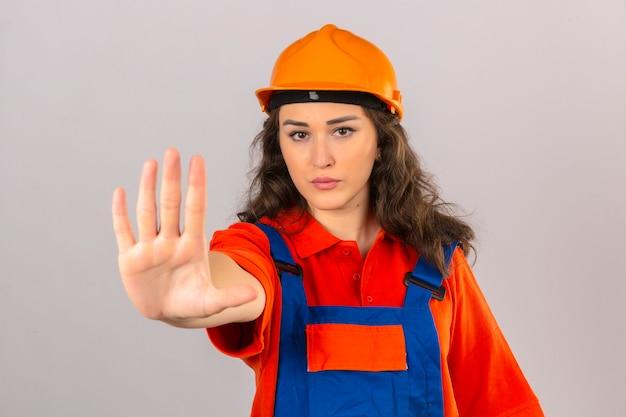 De jonge bouwersvrouw in eenvormige bouw en veiligheidshelm die einde doen zingen met palm van de uitdrukking van de handwaarschuwing over geïsoleerde witte muur