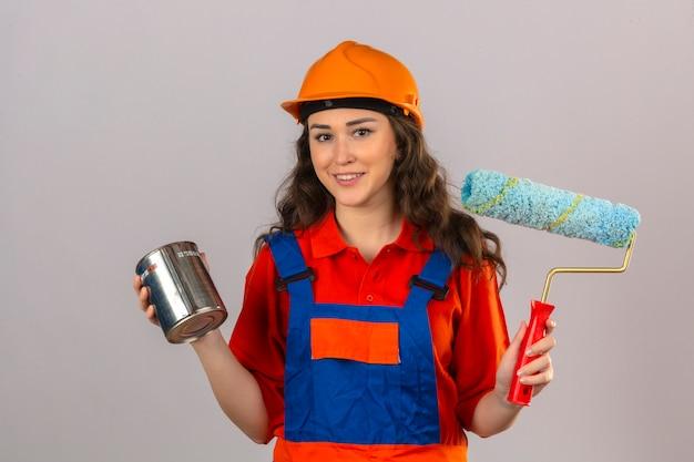 De jonge bouwersvrouw in eenvormige bouw en veiligheidshelm die zich met verfrol en verf bevinden kan vrolijk over geïsoleerde witte muur glimlachen