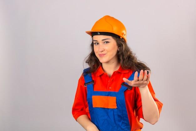 De jonge bouwersvrouw in eenvormige bouw en veiligheidshelm het vragen ontspannen nemen gemakkelijk opheffen de kalmtegebaar van de handgreep glimlachen vriendschappelijk over geïsoleerde witte muur