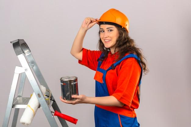 De jonge bouwersvrouw in eenvormige bouw en veiligheidshelm op een metaalladder met verf kan glimlachend en wat betreft haar helm over geïsoleerde witte muur glimlachen