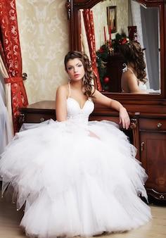 De jonge bruid bekijkt zichzelf in spiegel