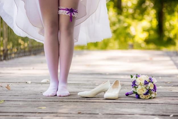 De jonge bruid in een witte jurk staat blootsvoets op een houten brug. schoenenmeisje en een boeket dat daar ligt. bruid die blootsvoets op de brug staat.