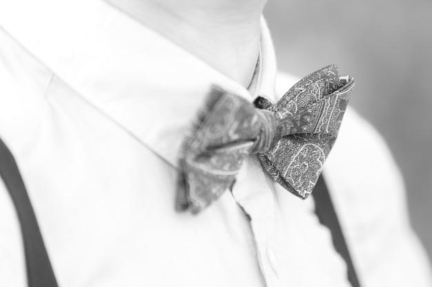 De jonge bruidegom op de huwelijksdag. de blauwe vlinderdas op de bruidegom. zwart en wit