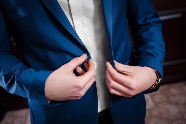 De jonge bruidegom op de huwelijksdag. hij knoopt de knopen van zijn jas dicht
