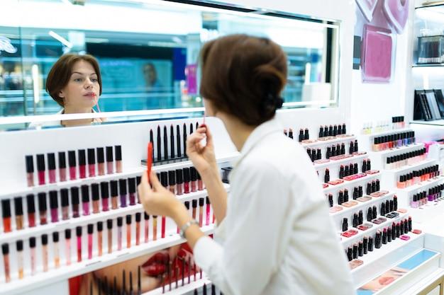 De jonge brunette bekijkt bezinning in producten van de missor de testende schoonheid