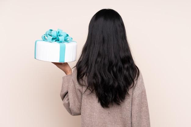 De jonge cake van de vrouwenholding over geïsoleerde muur