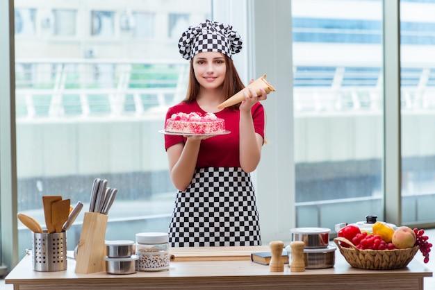 De jonge cake van het huisvrouwenbaksel in keuken