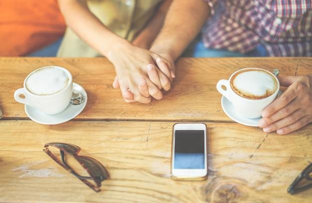 De jonge cappuccino van de paar roosterende koffie bij de winkel van de barcafetaria