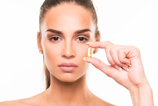 De jonge capsule van de vrouwenholding van collageen. concept van jeugdige gezonde huid, vitamines, supplementen, gezonde levensstijl.