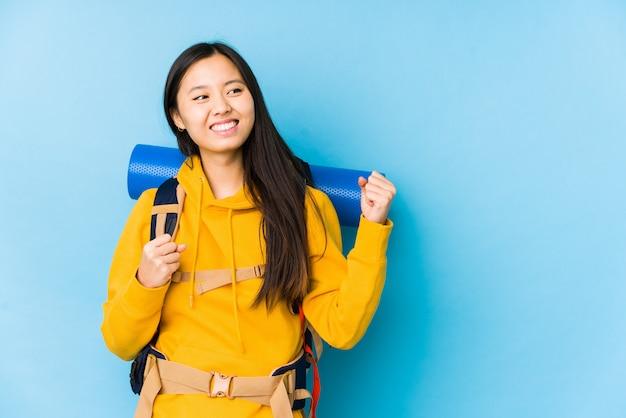 De jonge chinese backpackervrouw isoleerde het opheffen van vuist na een overwinning, winnaarconcept.