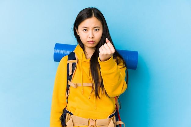 De jonge chinese backpackervrouw isoleerde tonend vuist met agressieve gelaatsuitdrukking.