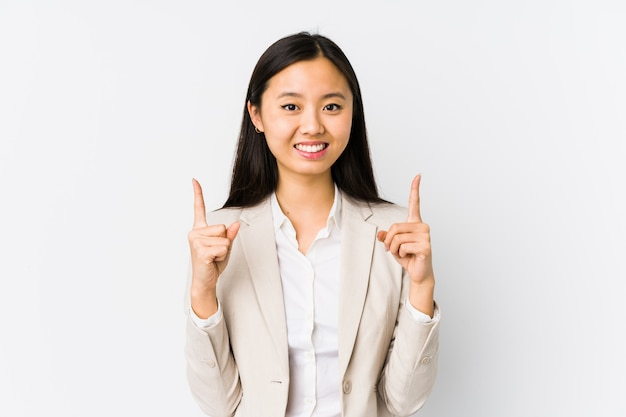 De jonge chinese bedrijfs geïsoleerde vrouw geeft met beide voorvingers aan die een lege ruimte tonen.