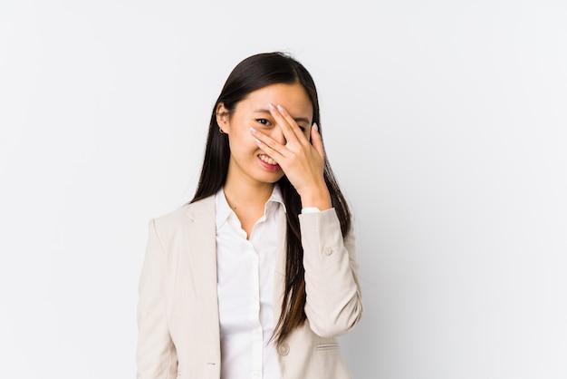De jonge chinese bedrijfsvrouw isoleerde knipoogje bij door vingers, beschaamd behandelend gezicht.