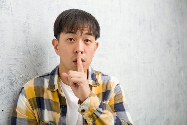 De jonge chinese close-up die van het mensengezicht een geheim houden of om stilte vragen
