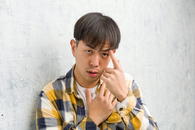 De jonge chinese close-up die van het mensengezicht een teleurstellingsgebaar met vinger doen
