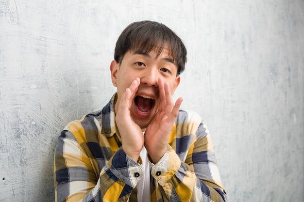 De jonge chinese close-up die van het mensengezicht iets gelukkig aan de voorzijde schreeuwen