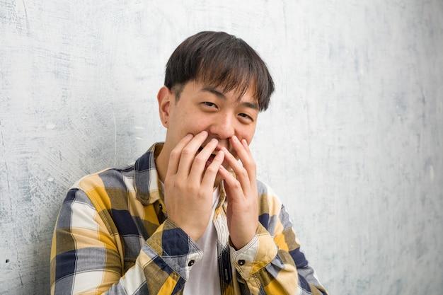 De jonge chinese close-up die van het mensengezicht over iets lachen, die mond behandelen met handen