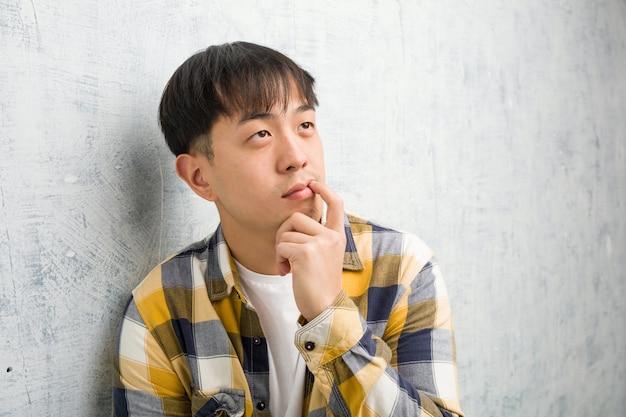De jonge chinese close-up van het mensengezicht betwijfelend en verward