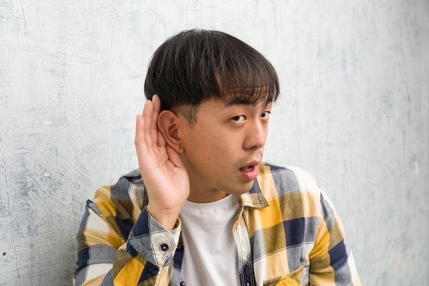 De jonge chinese close-up van het mensengezicht probeert aan het luisteren van een roddel