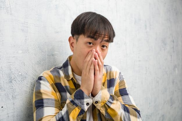 De jonge chinese close-up van het mensengezicht zeer doen schrikken en bang verborgen