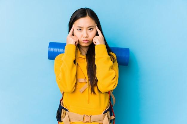 De jonge chinese geïsoleerde backpackervrouw concentreerde zich op een taak, houdend wijsvingers die hoofd richten.