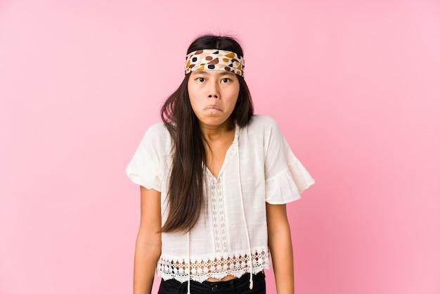 De jonge chinese geïsoleerde hippie haalt schouders op en verwarde ogen.