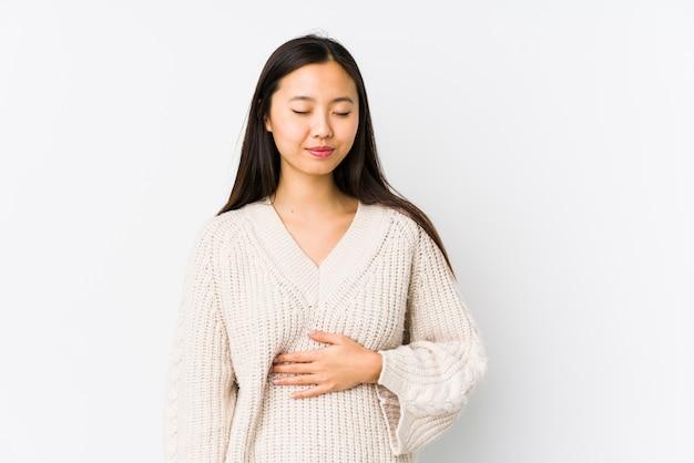 De jonge chinese geïsoleerde vrouw raakt aanrakingenbuik, zacht glimlachen, het eten en tevredenheidsconcept.