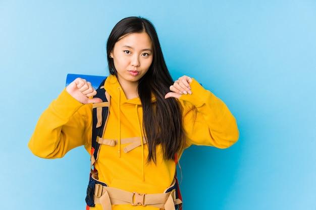 De jonge chinese geïsoleerde vrouw van de backpacker voelt zich trots en zelfverzekerd, voorbeeld om te volgen.