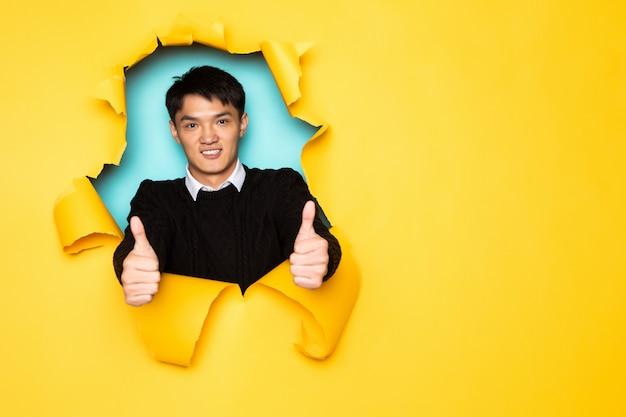 De jonge chinese mens met omhoog duimen houdt hoofd in gat van gescheurde gele muur. mannenhoofd in gescheurd papier.