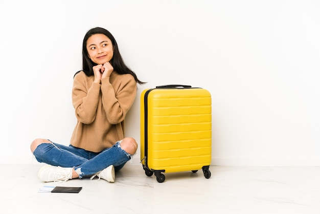 De jonge chinese reizigersvrouw die op de vloer zit met een geïsoleerde koffer houdt de handen onder de kin, kijkt gelukkig opzij.