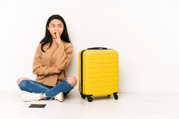 De jonge chinese reizigersvrouw die op de vloer zit met een geïsoleerde koffer zegt een geheim heet remmend nieuws en kijkt opzij