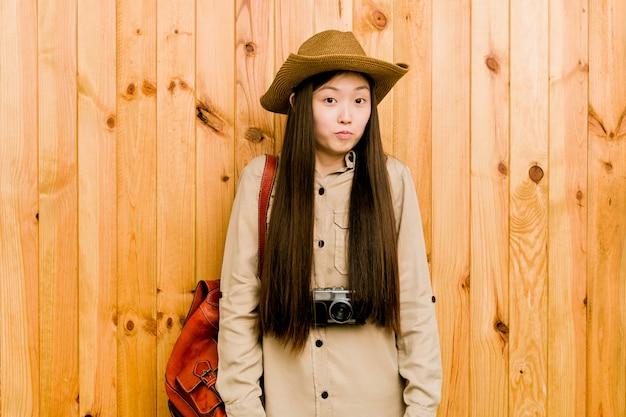 De jonge chinese reizigersvrouw haalt verwarde schouders en open ogen op.