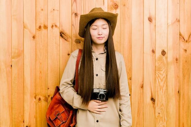 De jonge chinese reizigersvrouw raakt buik, glimlacht zacht, het eten en tevredenheid.
