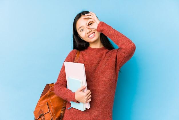 De jonge chinese studentenvrouw isoleerde opgewekt houdend ok gebaar op oog.