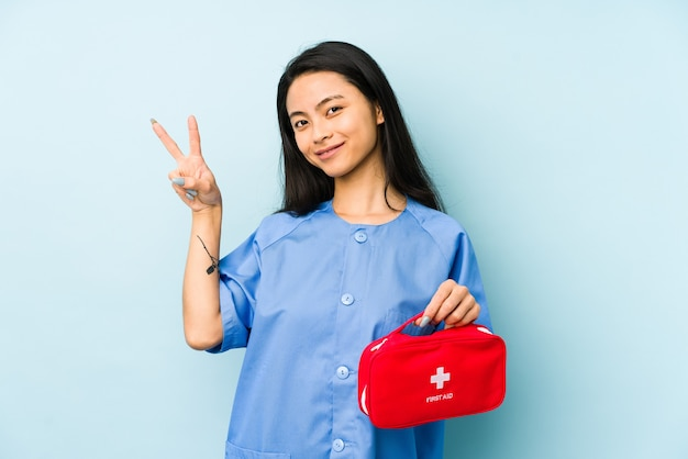 De jonge chinese verpleegstersvrouw die op een blauwe muur wordt geïsoleerd, kijkt opzij glimlachend, vrolijk en aangenaam.