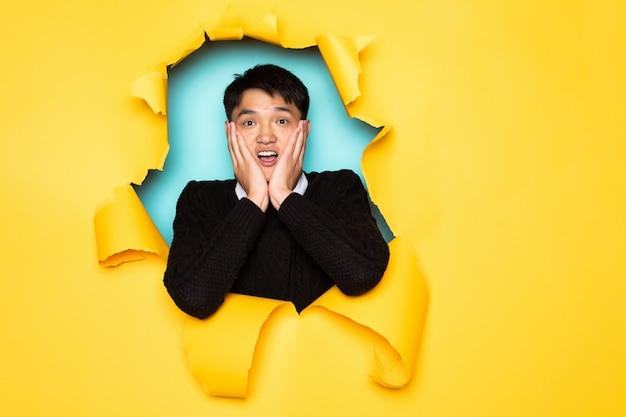 De jonge chinese verraste mens houdt hoofd in gat van gescheurde gele muur. mannenhoofd in gescheurd papier.