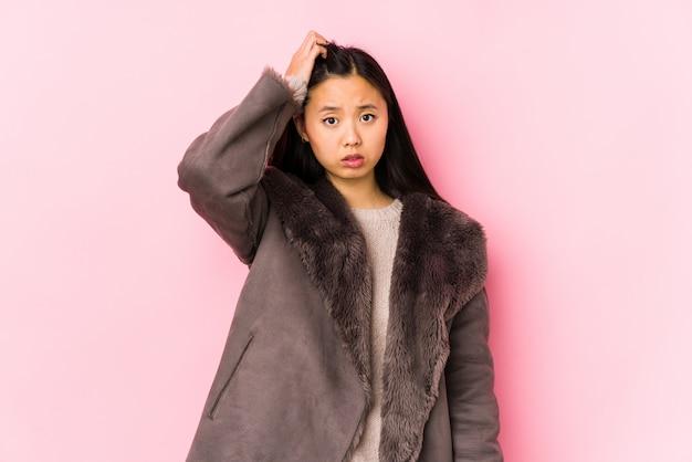 De jonge chinese vrouw die een geïsoleerde jas draagt wordt geschokt, heeft zij belangrijke vergadering herinnerd.