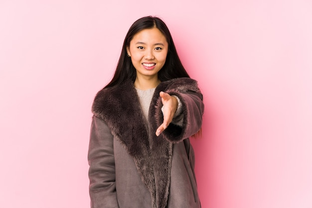 De jonge chinese vrouw die een laag geïsoleerd uitrekken zich draagt dient groetgebaar in.