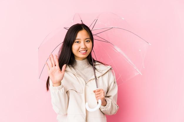 De jonge chinese vrouw die een paraplu geïsoleerd houden glimlachend glimlachend tonend nummer vijf met vingers.